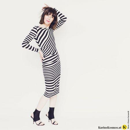 Frau in einem Kleid mit weiß/schwarzen Streifen.
