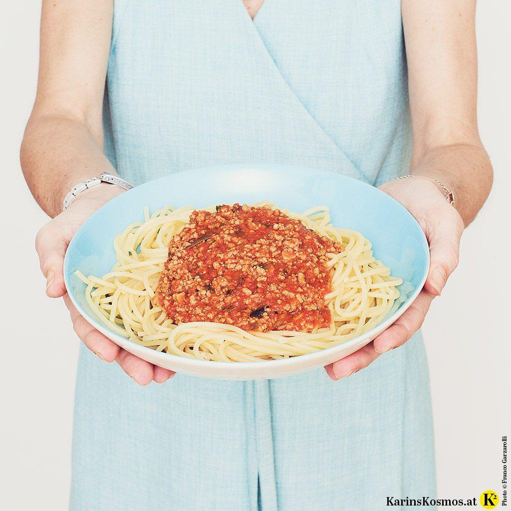 Frau in einem Türkisen Wickelkleid hält einen Teller mit Spaghetti Bolognese.