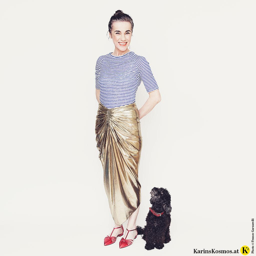 Frau in Streifenshirt, goldenem Rock und flachen Schuhen. Daneben sitzt ein schwarzer Toypudel.