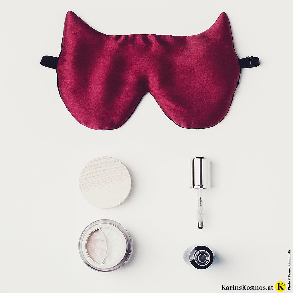 Produktfoto mit Augenmaske aus Seide, Augencreme und Serum gegen geschwollene Augen.