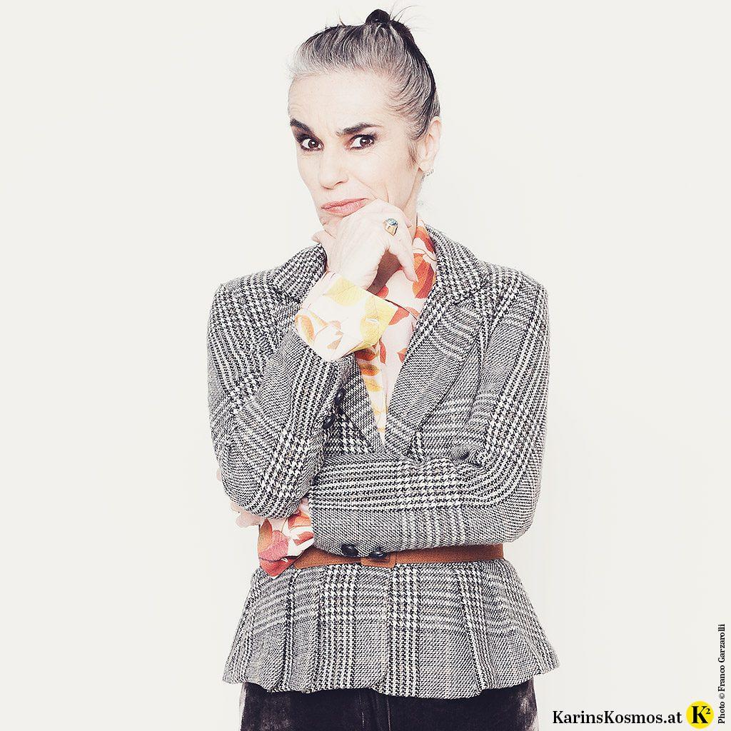 Frau in einem Karo-Blazer zu einer bunten Bluse mit Blätter-Print.