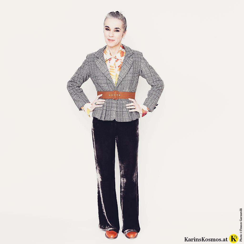Frau in einem Karo-Blaser mit Stoffgürtel und einer Bluse mit Blumenprint darunter. Dazu trägt sie eine Samthose und Leder-Schnürer.