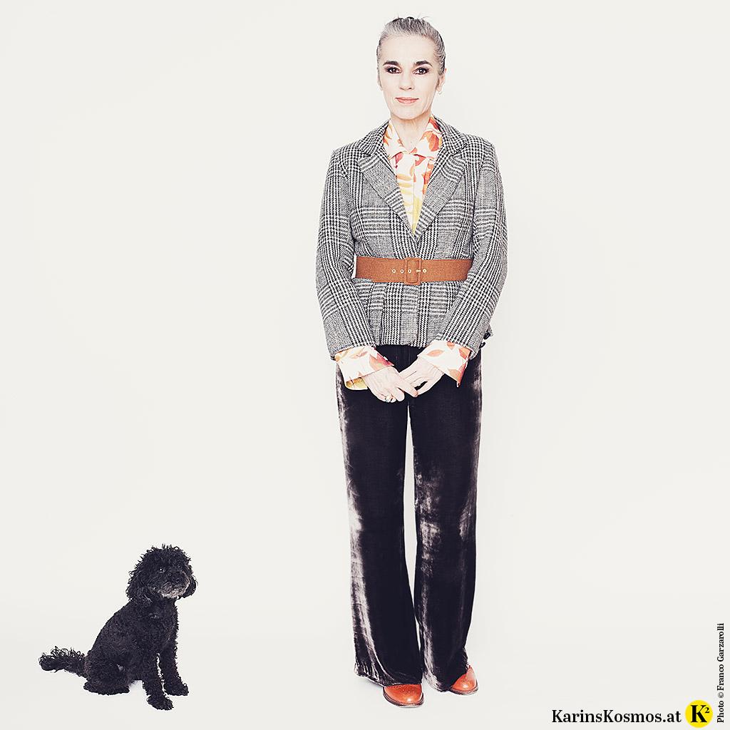 Toypudel Trudy sitzt neben Frauchen Karin Garzarolli. Diese trägt einen Karo-Blazer zur Samthose.