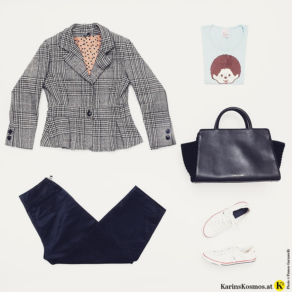 Produktfoto mit schmal geschnittenem Blazer mit Karo Muster, Print-Shirt, schwarzer Hose, Sneakers und XL-Bag.
