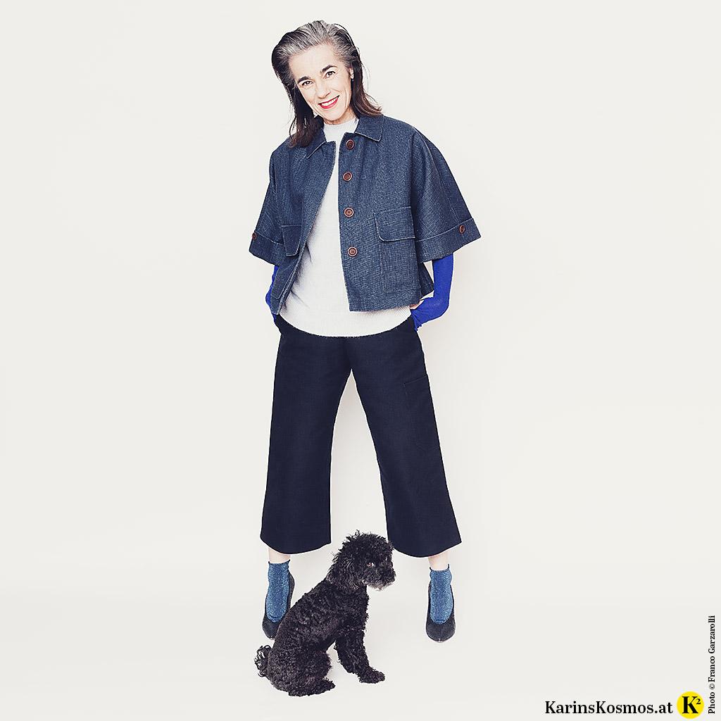 Foto von einer Frau, die ein Outfit in Blau trägt mit einem kleinen Toypudel.
