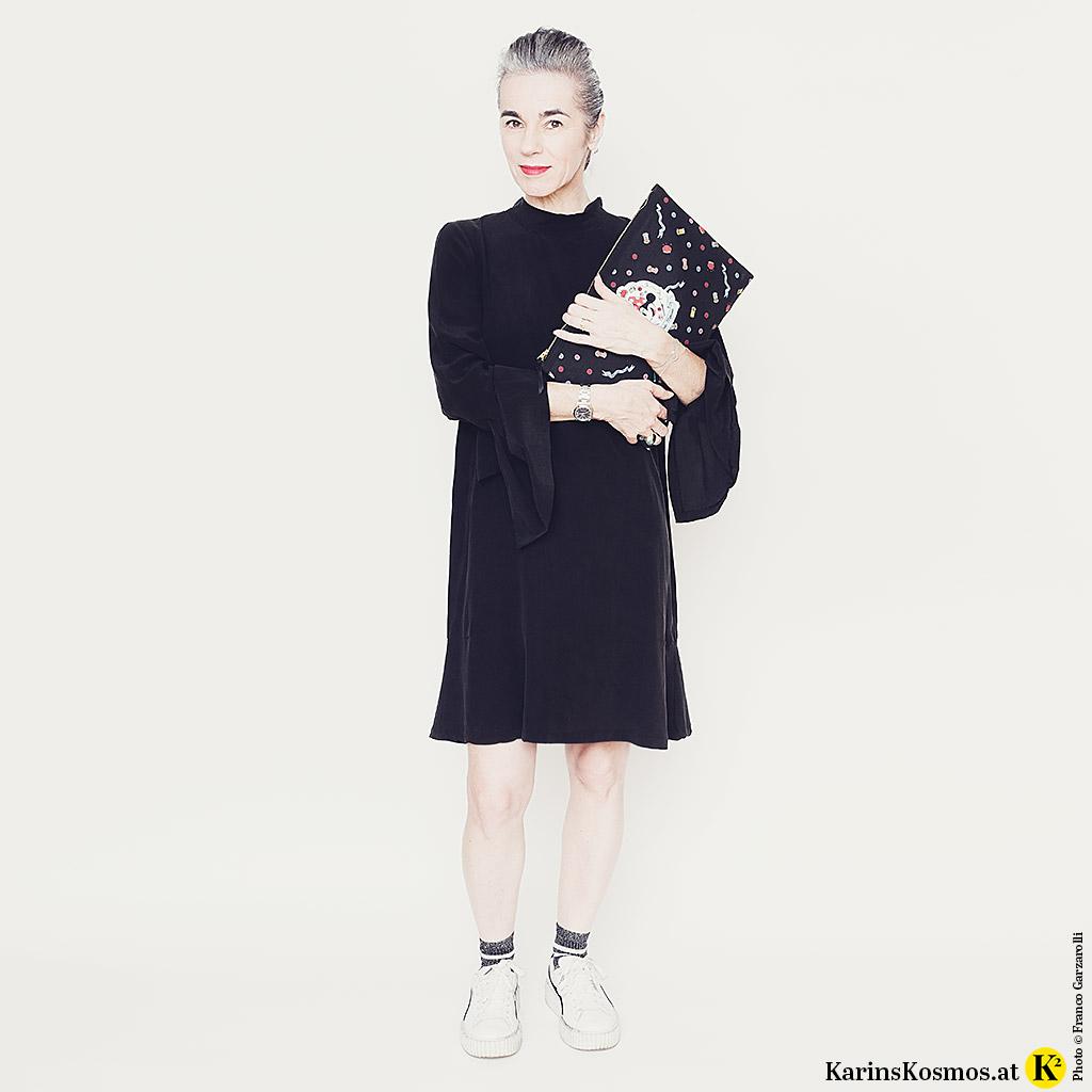 Frau im kleinen Schwarzen aus Seide zu Sneakers mit einer Clutch.