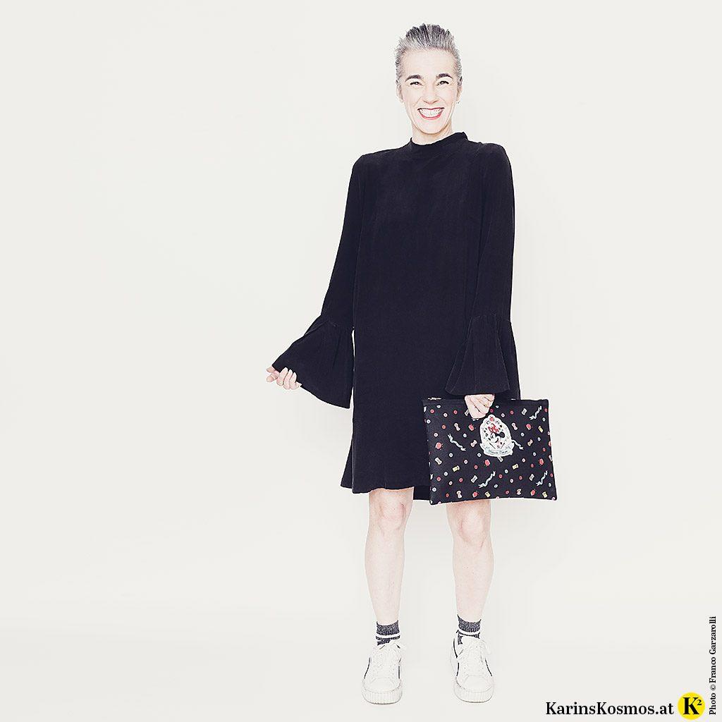 Eine Frau trägt das kleine Schwarze aus Seide mit Turnschuhen dazu.