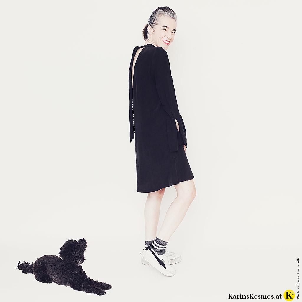 Frau in einem Kleid aus schwarzer Seide mit Turnschuhen. Daneben liegt ein schwarzer, kleiner Pudel.