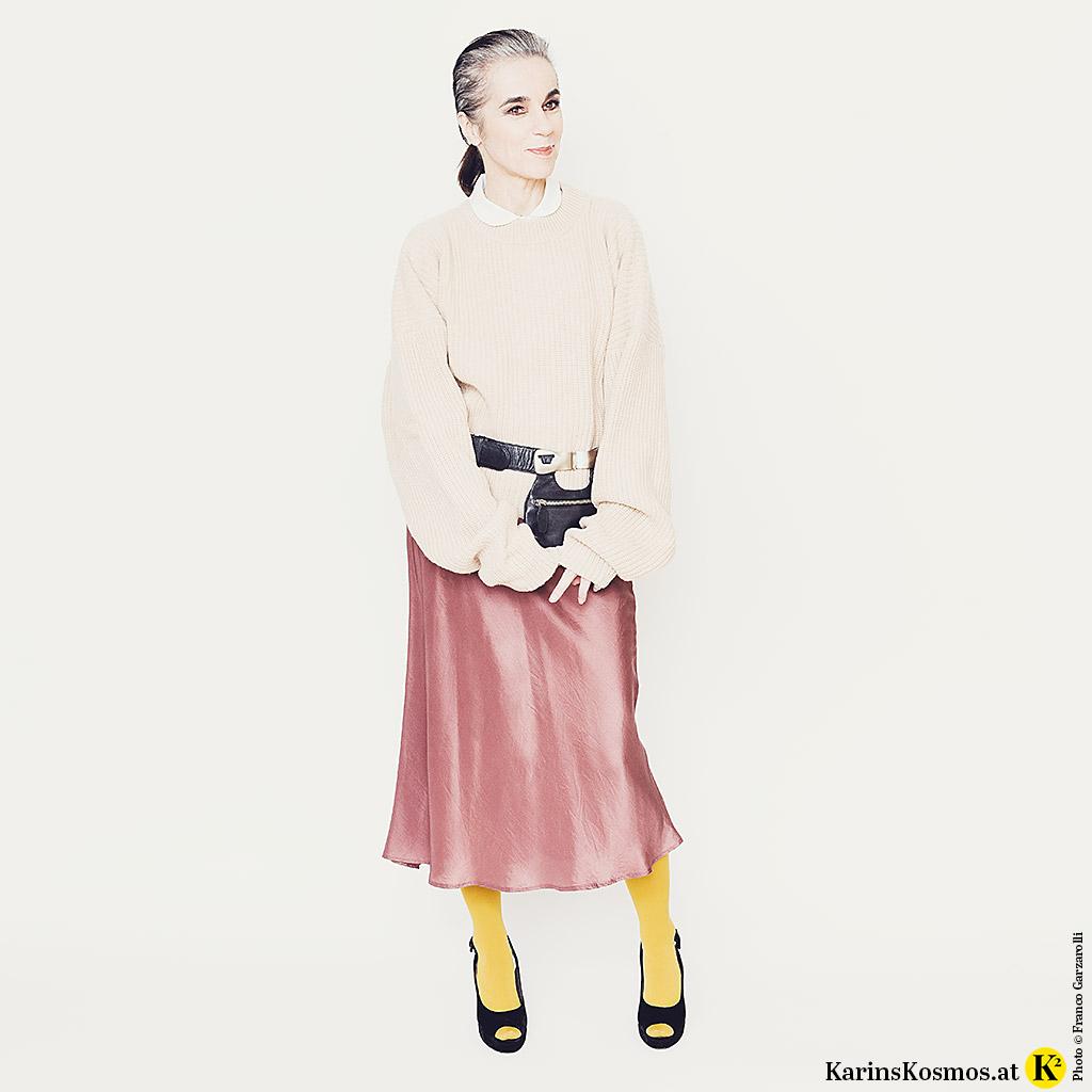 Frau gekleidet im Materialmix aus Samt, Seide und Strick.