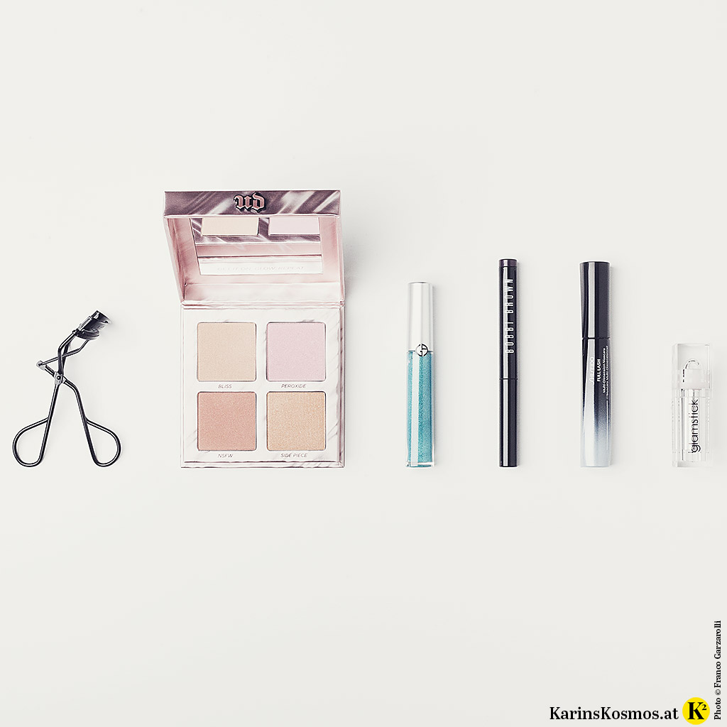 Produktefoto mit Wimpernzange, Highlighter-Palette, Lidschatten, Wimperntusche und Lippenstift für das 20er-Jahre Make-up.