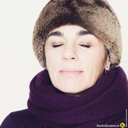 Foto von einer Frau mit Schal, Mütze und Winter-make-up.