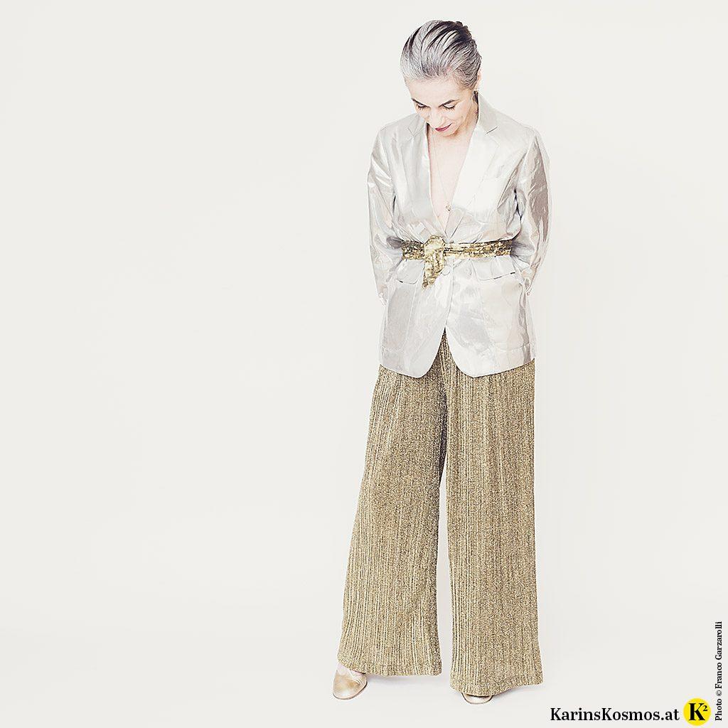 Frau in Metallic-Mode in Form eines Blazers in Hochglanzsilber und Goldhose.