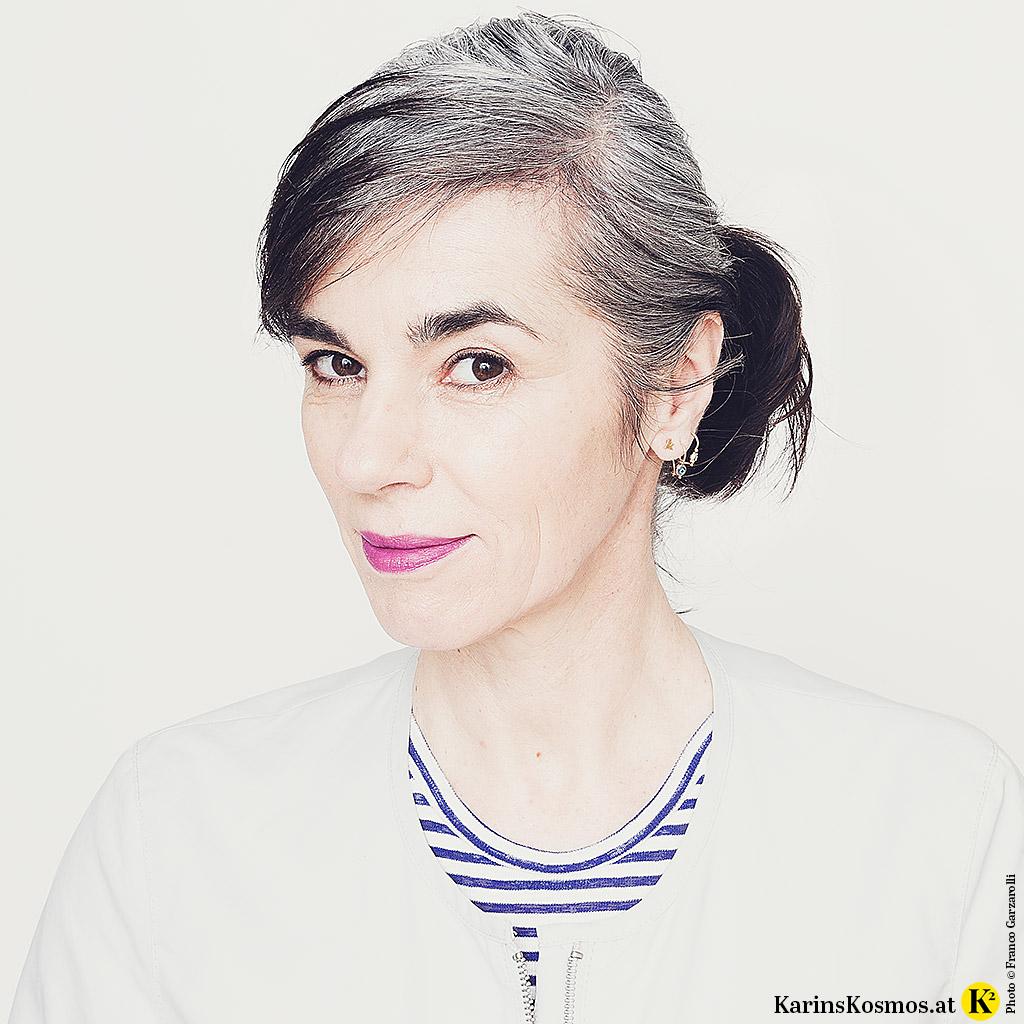Frau mit ca. zehn Zentimeter langem Haaransatz in Grau.