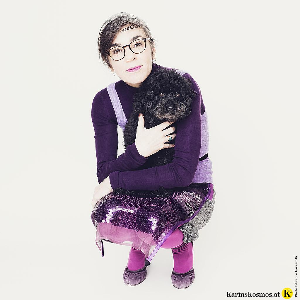 Frau in einem Outfit in Ultraviolett mit kleinem Toypudel am Arm.