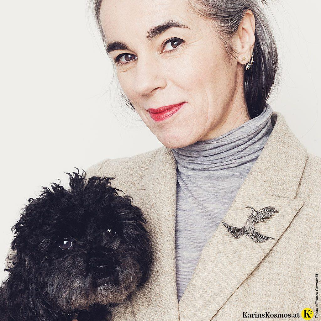 Frau mit einem Blazer und Vintage-Brosche am Revers. Am Arm trägt sie einen schwarzen Pudel.