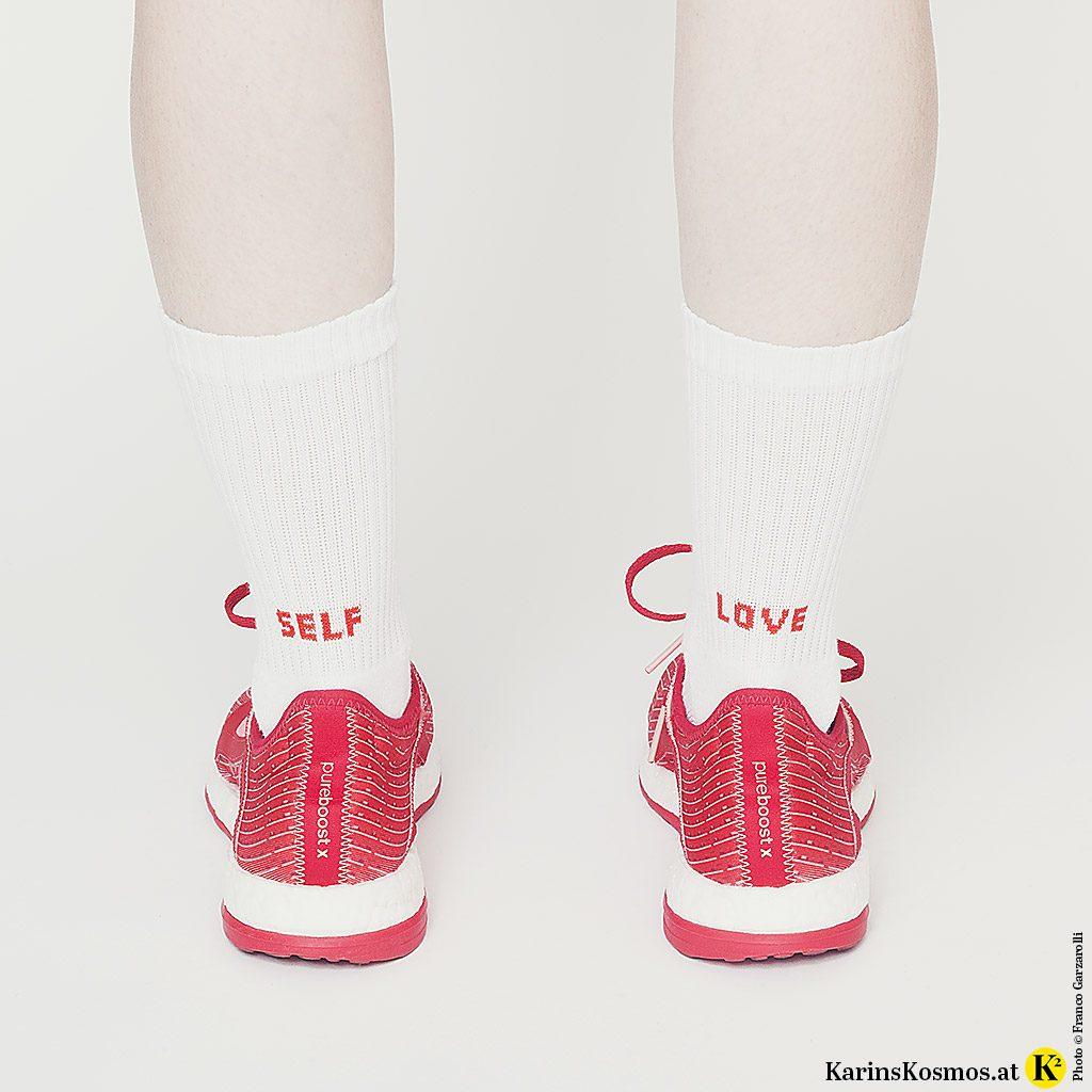 """Frau mit Turnschuhen an und Socken mit der Aufschrift """"Self Love"""". Es geht hier um stop smoking."""