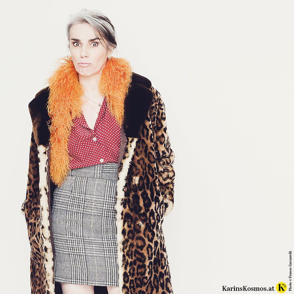Frau in einer getupften Seidenbluse zu kariertem Rock, Mantel in Leoprint und orangen Fellschal – kurzum im wilden Mustermix!