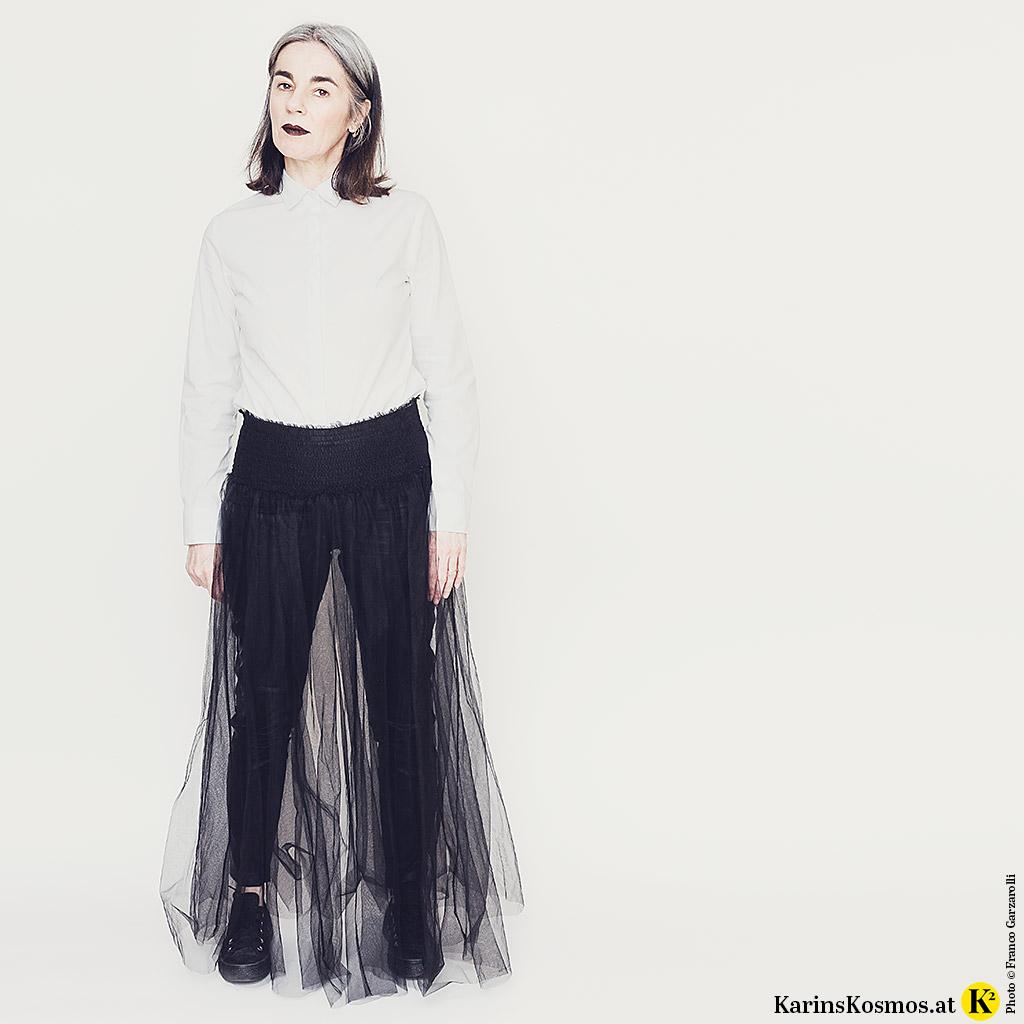 Frau in weißer, hochgeschlossener Bluse zu Lederhose und Tüllrock darüber. Dazu trägt sie Sneakers.