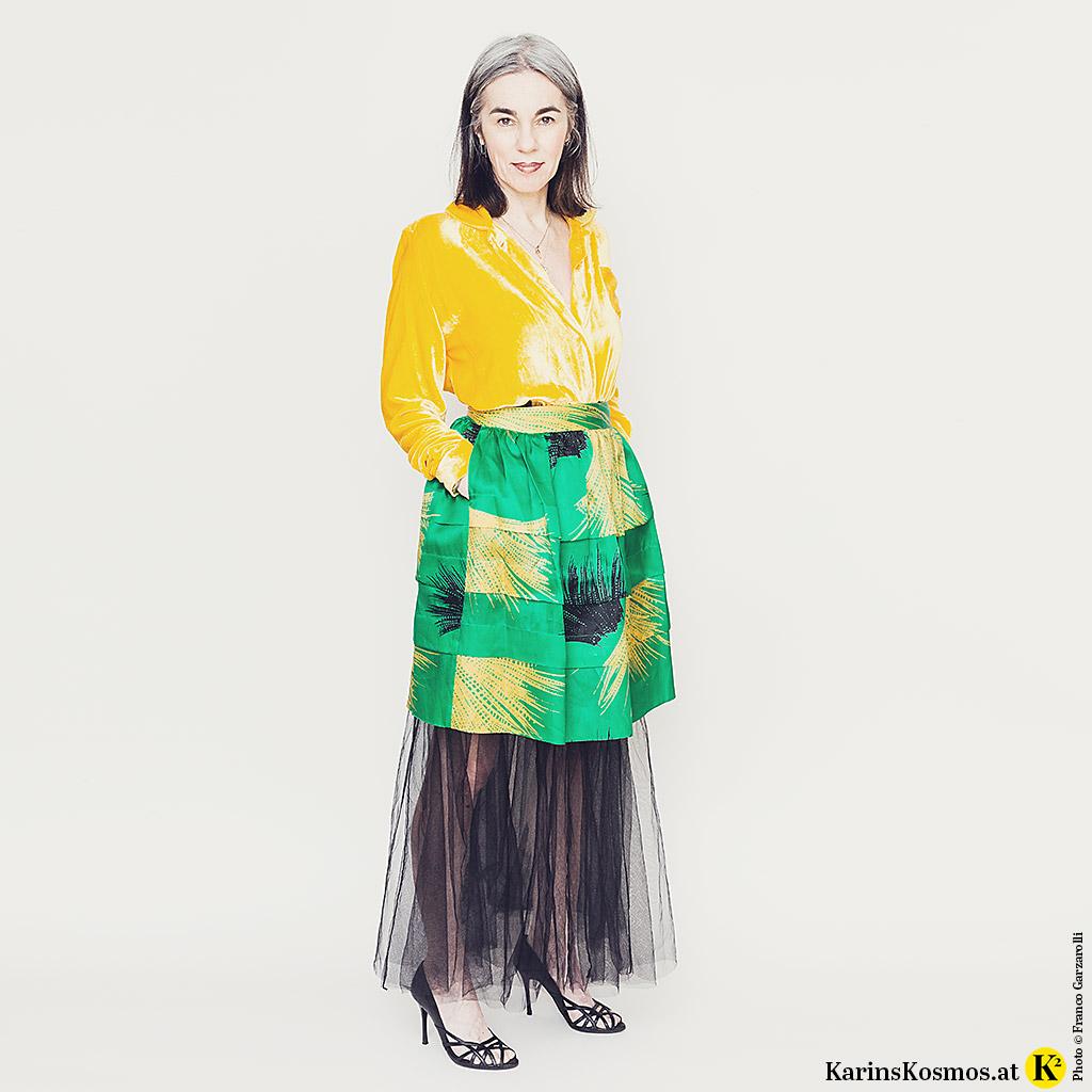 Frau in einer gelben Samtbluse zu kurzem Seidenrock und langem Tüllrock darunter.