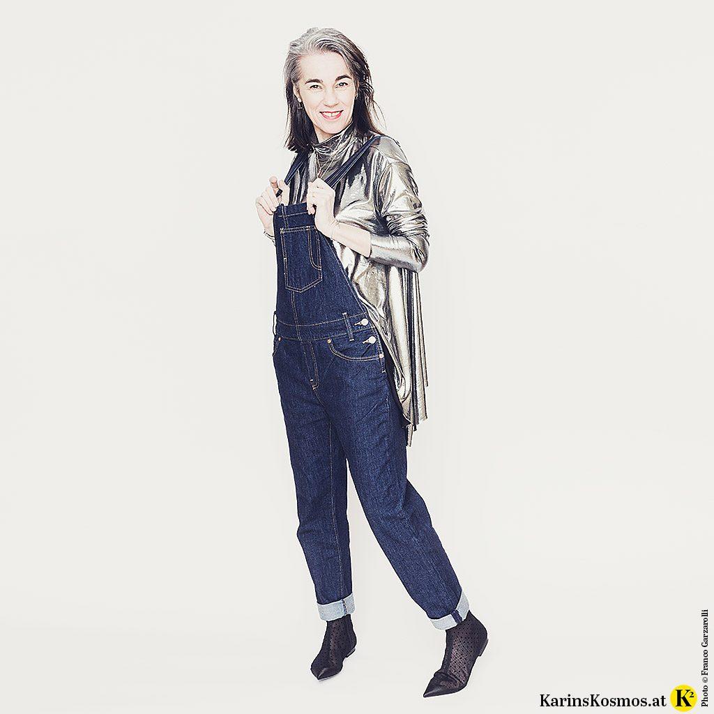 Frau in einer Jeanslatzhose, dazu trägt sie ein silberfarbenes Top und Stoff-Stiefeletten.