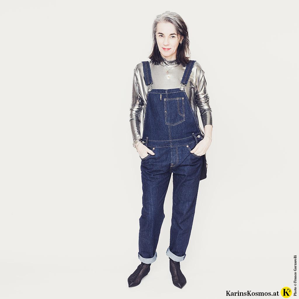 Frau in einer Jeans-Latzhose. Dazu trägt sie eine silberfarbenes Oberteil und Stiefeletten aus Stoff.