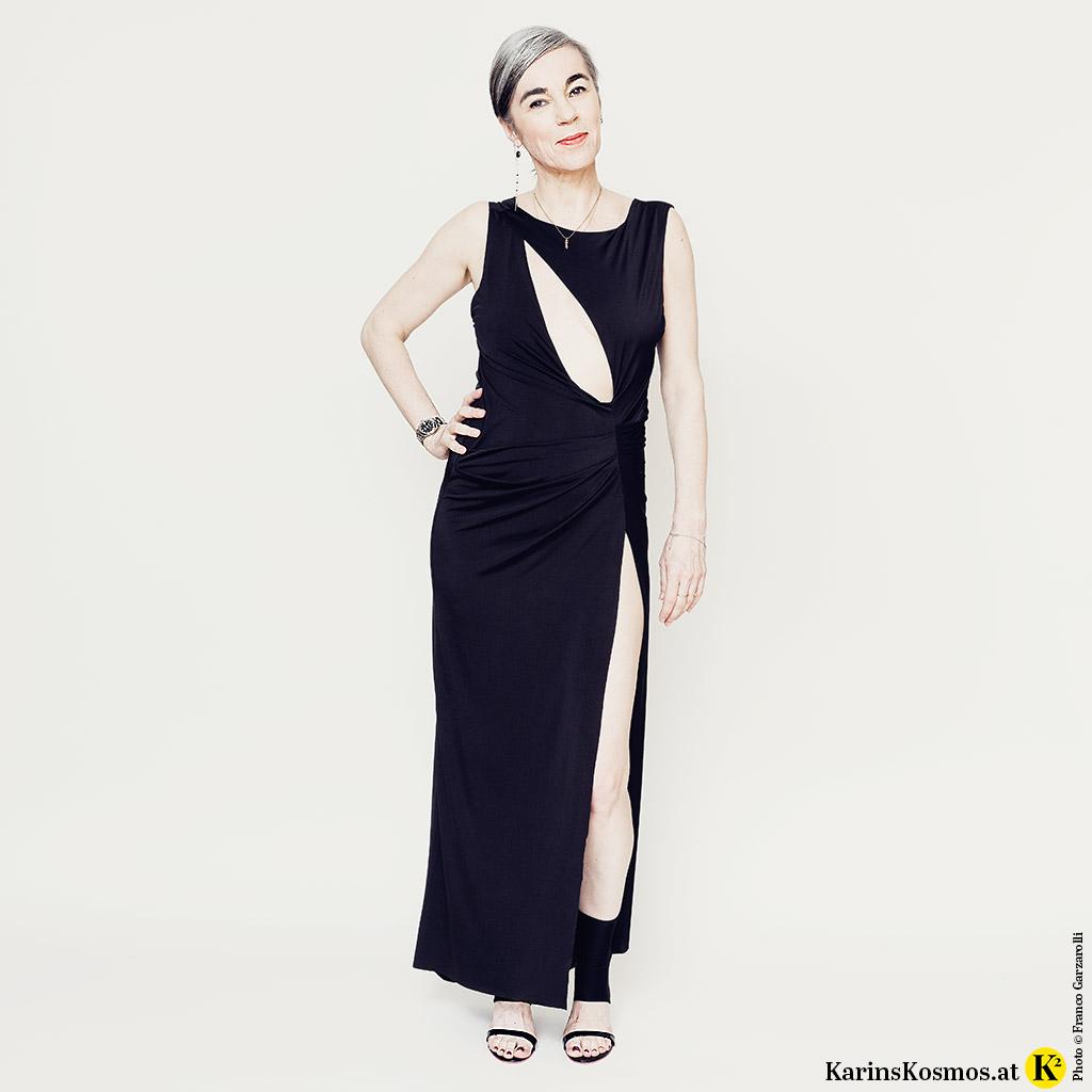 Frau in einem schwarzen Abendkleid, in dem man am Red Carpet auftreten kann.