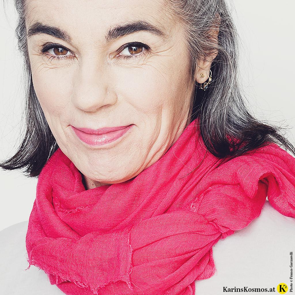 Frau mit natürlichem Make-up und einem pinken Tuch, das sie gerne auf Reisen verwendet.