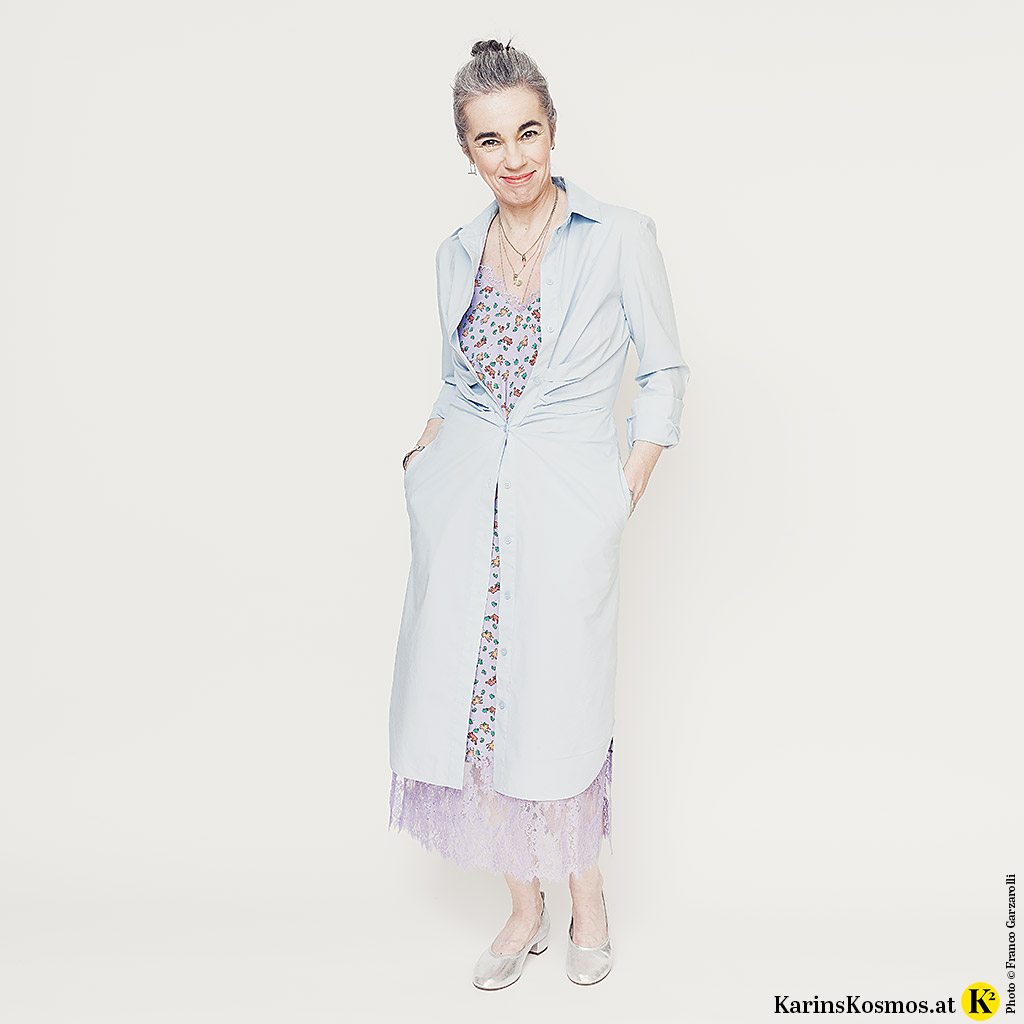 Frau in einem Hemdblusenkleid über einem Slipdress als Mantel getragen. Dazu trägt sie Pumps.