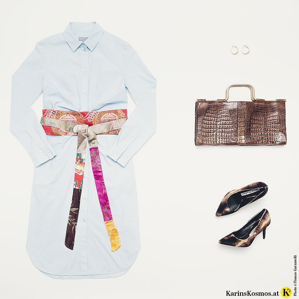 Produktstilllife mit Hemdblusenkleid, Seidengürtel, Ledertasche und Pumps.