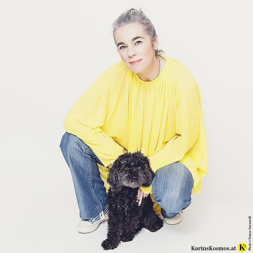 Karin Garzarolli in Flared Jeans mit gelbem Kleid und ihrem schwarzen Toypudel.