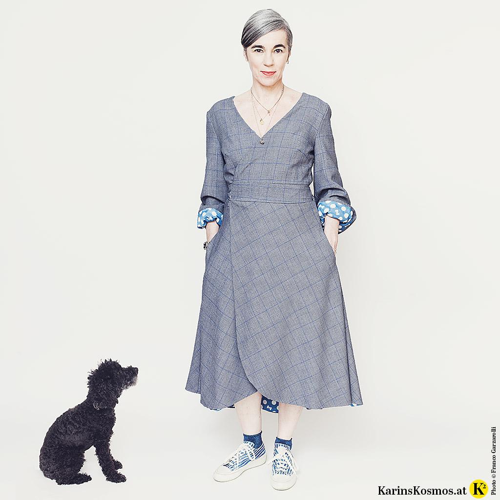 Frau in einem Wickelkleid steht und daneben sitzt ein kleiner Zwergpudel.
