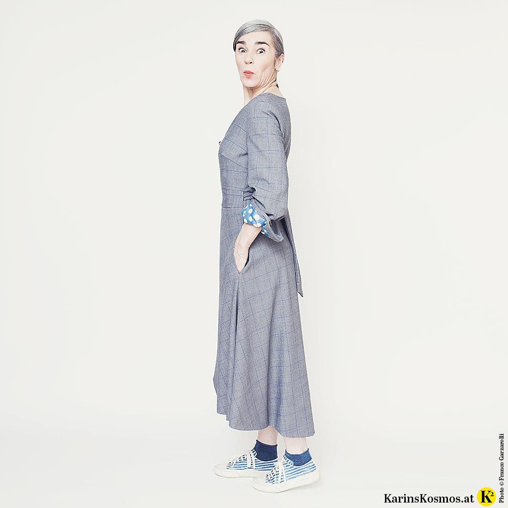 Frau in einem Wickelkleid, seitlich fotografiert. Dazu trägt sie kurze Socken und Sneakers.