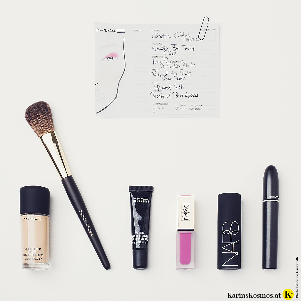 Produktfot mit Make-up-Produkten wie Foundation, Pinsel, Lippenstift, Rouge und Wimperntusche.